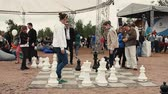 Girl moves big chess figure on game field on ground. Summer festival. People