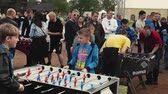 Two teens absorbedly play american table soccer among other. Summer festival