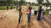 Little boy play jenga game with adult dad on sand. Tower fall. Summer festival.