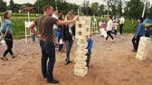Little boy play big jenga game with mom and dad on sand. Summer festival. People Stok Video
