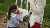 Back side of little girl draws picture on easel in park on summer festival.