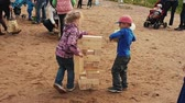 Little boy and girl play big jenga game on sand. Summer festival. People, kids
