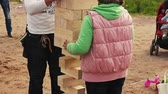 Girl play big jenga game with adult man on sand in park. Summer family festival