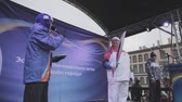 feier : Relay race Sochi Olympic torch in Saint Petersburg in October 2013. Host in purple jacket, warm hat with microphone on stage. Torchbearer with not burning flame