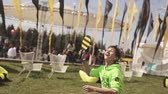 aile : Happy boy play tennis on summer festival. Sunny day. Black and yellow flags. Entertainment. People. Slow motion
