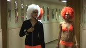 peruca : Girls in orange bikini and wigs walk through corridor, look in camera. Go go dancers. Man in scary mask.