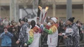 first : SAINT PETERSBURG, RUSSIA - OCTOBER 27, 2013: Relay race Sochi Olympic flame. Russian TV star Tina Kandelaki pass flame to footballer Alexander Kerzhakov. Wave hands to people. Slow motion