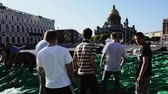 carry out : Men building stage for event on street. Workers carry huge green tent. Saint Petersburg. Sunny day.