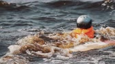 splashing : CLose up of a boy in helmet and orange life vest on a wakeboard pulled out of water with stretched rope