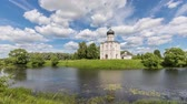 russian federation : Church of the Intercession on the Nerl reflecting in water on sunny day with scenic clouds in Bogolubovo, Vladimir oblast, Russia