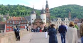 Heidelberg, Germany - May 14 2017: People walk on Old Bridge (Alte Brucke) in front of the Bridge Gate (Bruckentor)