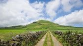 Rural landscape with country road and extinct volcanic crater on backgrount, Sao Miguel island, Azores, Portugal (time lapse video) Stok Video
