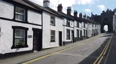 wales : Footage of a row of cottages on a street in Conwy and the town Castle walls. Stock Footage