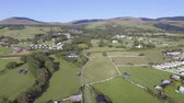 a view : This aerial shot shows the small village of Talybont and hills and mountains in the background on a sunny day. The shot then descends to reveal more of the lower landscape.