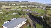 a view : This short aerial shot flies over the camping field and farm house in Talybont, North Wales. It is a sunny day and the Welsh hills and mountains can be seen in the background. Stock Footage