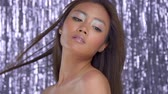 mixed race person : commercial portrait of asian model with disco party makeup on silver rain background. Slowmotion from 60 fps, blowing hair