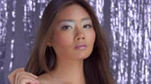 smíšený : thai asian model in studio with silver rain disco background watching aside. ideal skin party makeup