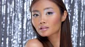 глэм : pretty asian young model with party makeup poses to a camera