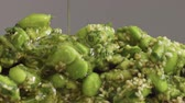 sprinkled : mix of edamame with sesame seeds and avocado and olive oil pouring on it. Green veggie food concept. Closeup edamame mix Stock Footage
