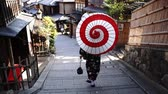 geisha : woman wearing a kimono walks in Kyoto Japan