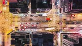 ingázó : 4K UHD Time-lapse of car traffic on road and people crossing street at night in Hong Kong downtown district, drone aerial top view. Commuter, Asia city life, or public transportation concept, Panning
