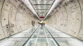 ingázó : 4K UHD time-lapse of unidentified people walking in subway tunnel walkway, zoom out then still. Underground public transportation, futuristic architecture, city life, or commuter lifestyle concept Stock mozgókép