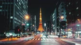 ingázó : 4K UHD time-lapse of illuminated Tokyo tower, car traffic transport at night. Japan landmark and transportation, Tokyo tourist attraction, Asian city life, or Asia tourism concept. Zoom in then still