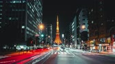 ingázó : 4K UHD time-lapse of illuminated Tokyo tower, car traffic transport at night. Japan landmark and transportation, Tokyo tourist attraction, Asian city life, or Asia tourism concept. Zoom out then still