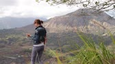 batur : Young woman with smartphone and backpack on a beautiful mountain background. Volcano Batur, Bali. Stock Footage