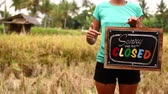 вывеска : Woman hands with closed sign board on a tropical nature background. Bali island.