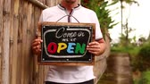 スレート : Open sign board in a man hands on a tropical nature background. Shooted on Bali island, full HD.