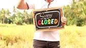 desolé : Man hands with closed sign board on a tropical nature background. Bali island.