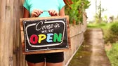 スレート : Open sign board in a woman hands on a tropical nature background. Shooted on Bali island, full HD. 動画素材