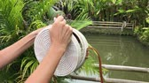 kabelka : Woman hands with stylich eco friendly rattan bag on a tropical background. Bali island.