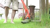 Strimming grass with an electric grass cutter Stock Footage