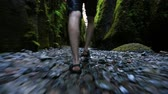 sandálias : v4. Glide cam shot of male walking through small creek at low angle. Stock Footage