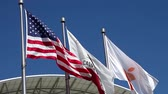 multinationale : Cupertino, CA, USA - August 15, 2016: close up of flags in front of Apple Headquarters with American Flag and flag with Apple icon. Vidéos Libres De Droits