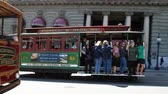 vezetett : San Francisco, California, United States - August 17, 2016: Classic cable cars on wheels with guided tour carrying tourists in front of Westin St. Francis hotel along the famous Powell Street. Stock mozgókép