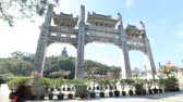 porta de entrada : Hong Kong, China - December 11, 2016: Time lapse of scenic gateway in a sunny day of Po Lin Monastery and the Big Buddha on background, icon and symbol of Lantau Island, popular tourist destination.