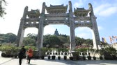 porta de entrada : Hong Kong, China - December 11, 2016: Time lapse of tourists visiting Scenic gateway of Po Lin Monastery and the Big Buddha, icon and symbol of Lantau Island, popular tourist Chinese destination.