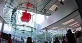 observar : Hong Kong, China - December 4, 2016: fish eye wide panorama of Red Apple sign and glass spiral staircase in Apple store, IFC Mall, Observation Ferris Wheel at Victoria Harbour skyline on background.