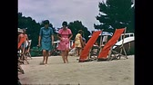 calçada : Ibiza, Spain - circa 1973: Two tourist women in vintage clothing playing with the sand on holiday on the beach of Bay of Portinatx in 70s. Vintage restored footage.
