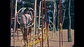 calçada : Ibiza, Spain - circa 1973: Tourist children on holiday playing with beach public carousel of the beach in 70s. Vintage restored footage. Stock Footage
