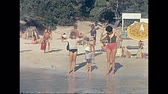 calçada : Ibiza, Spain - circa 1973: Historical restored footage on the beach of Bay of Portinatx. Tourists families on holiday going to bath in the sea with typical 70s vintage swimsuit. Stock Footage