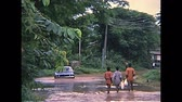 hetvenes évek : LAGOS, NIGERIA, AFRICA - 1976: Dirt roads of the town in a typical seasonal flood. A blue Mitsubishi Galant driving on dirt roads with high water. Local black Nigerian people walking in the mud. Stock mozgókép