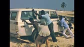 křižník : LAGOS, SOUTHERN NIGERIA, AFRICA - 1976: old historical footage of vintage Charlotte Toyota Land Cruiser stuck in the sand of the beach in Lagos with black Nigerian people pushing to take it out.