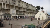 federal : San Francisco, United States - August 14, 2016: Alcatraz penitentiary sally port. Main building with guard tower, theater, ranger station and bookstore. Dock full of tourists waiting for boat. Stock Footage