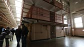 vezetett : San Francisco, United States - August 14, 2016: Alcatraz prison main room with three rows of cells on three levels. Many tourists visiting on tour every day. San Francisco historical landmark.
