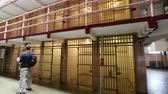 vezetett : Alcatraz prison, San Francisco, United States - August 14, 2016: main room with three rows of cell blocks on three levels.Panoramic view with people on tour.Popular tourist attraction in San Francisco Stock mozgókép