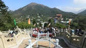 fiel : Hong Kong, China - December 11, 2016: Time lapse of procession of faithful people and Buddhist monks at Big Buddha, religious icon of Hong Kong on Lantau Island.